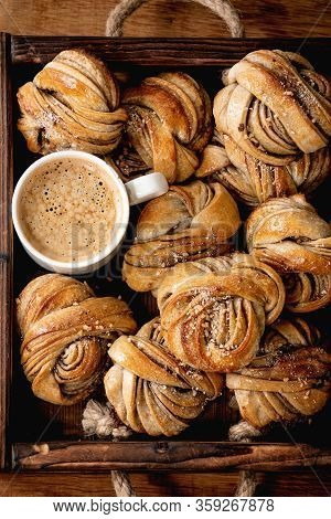 Traditional Swedish Cardamom Or Cinnamon Sweet Buns Kanelbulle In Wooden Tray, Cup Of Coffee On Wood