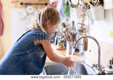 Kid Washing Hands At Home Under Water Tap. Cute Child Girl In Flour After Cooking In Cozy Home Kitch