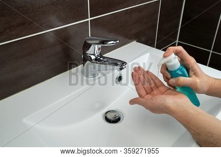 Person Washing Hands With Hand Sanitizer In A Loo Bathroom Toilet Because Of Coronavirus Covid-19Per