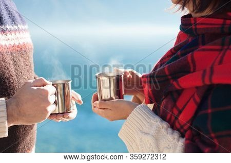 Couple In Love Drink Coffee. Winter Picnic At Sea Beach. Travelers Hold Camping Cups With Steamy Tea