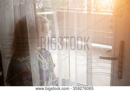 A Girl Locked In A House Looks Out The Window. Self-isolation From The Virus