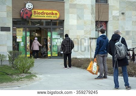 Warsaw, Poland. 3 April 2020. People Waiting In Line In Front Of A Supermarket At A Safe Social Dist