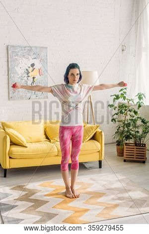 Tense Woman With Colorful Hair Holding Dumbbells With Outstretched Hands In Living Room
