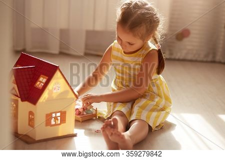 Little Girl Playing With Doll House While Siiting On Floor In Bedroom. Role Game For Young Children.