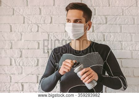 Young Fitness Man Wearing Medical Face Mask For Personal Protection And Holding Bottle Of Water. Con