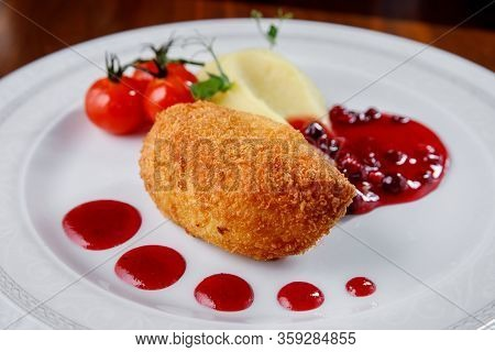 Kiev Chicken Cutlet With Mashed Potatoes And Berry Sauce On A White Plate.