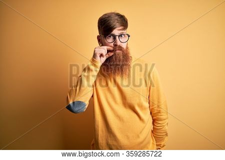 Handsome Irish redhead man with beard wearing glasses over yellow isolated background mouth and lips shut as zip with fingers. Secret and silent, taboo talking