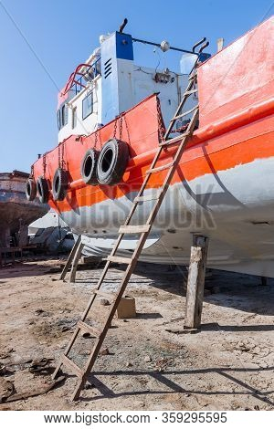 Old Rusty Orange Vessel Under Repair Located On Grungy Dry Dock In Shipyard Against Blue Sky On Sunn