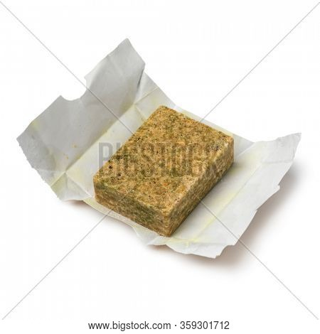 Single vegetarian Bouillon cube on paper isolated on white background