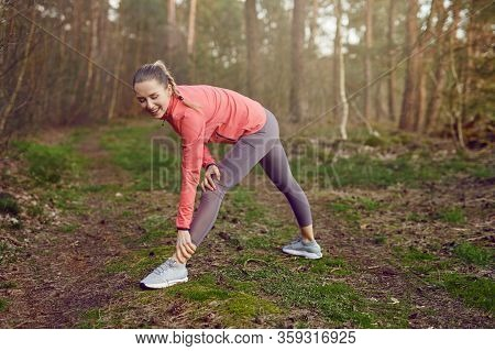 Full Length Portrait Of A Cheerful Fit Young Woman Doing Stretching Exercises For Legs And Arms Duri