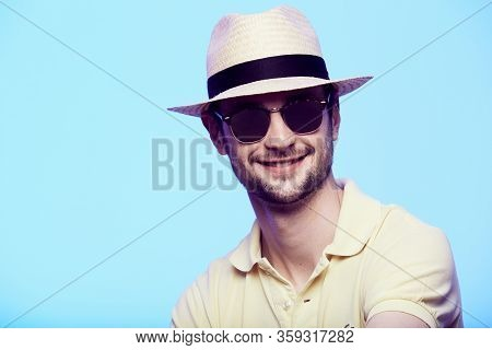 Closeup Portrait Of Awesome Hipster Wearing Fedora Hat With Intense Look At Camera. Headshot Over Bl