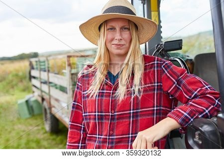 Young woman as a winegrower or vintner trainee leans on a tractor