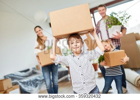Boy carries a moving box when moving with the family in the new house