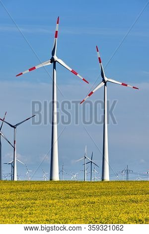 Field With Oilseed Rape And Wind Turbines In The Back Seen In Germany
