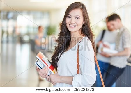 Woman as asian student in university with books