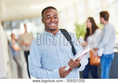 African student holding notebook in university school