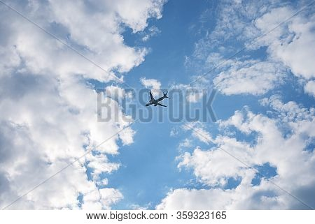Dark Silhouette Of The Set Off Plane On Background Of Beautiful Blue Sky In The Gap In White Fluffy