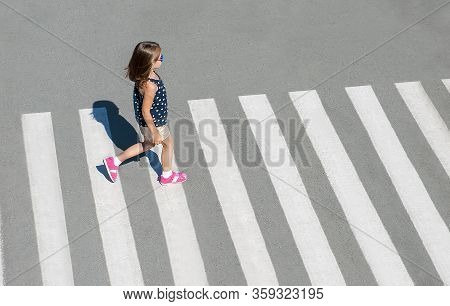 Stylish Child In Fashion Clothes Is Walking Along Summer City Crosswalk. Kid On Pedestrian Side Walk