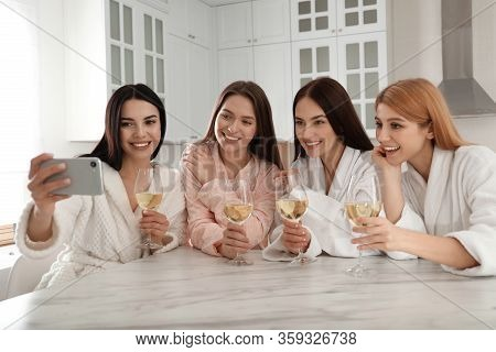 Beautiful Young Ladies With Wine Taking Selfie In Kitchen At Pamper Party. Women's Day