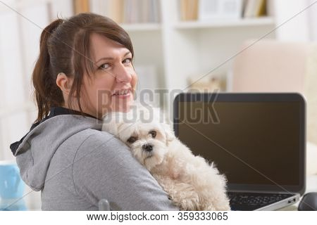 Hearing impaired woman working on laptop with her dog in hands at home office