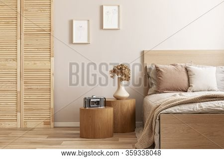 Vintage Camera On Round Wooden Nightstand Next To Cozy Single Bed