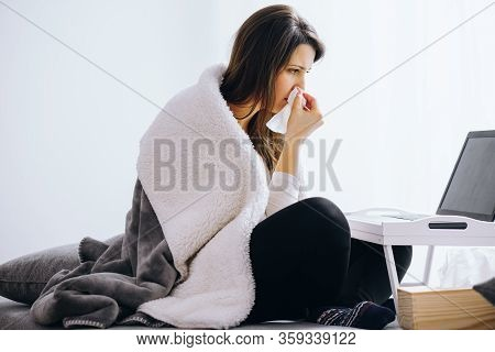 Sick Young Woman With Cold Sitting On The Floor Of Her Apartment