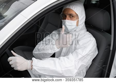 Man In Protective Suit, Medical Mask And Rubber Gloves For Protect From Bacteria And Virus Is Sittin