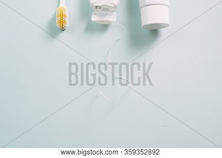 Dental Cleaning Tools And Hygiene Products On Blue Background With Copyspace. Toothbrush, Floss And