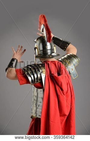 Roman soldier facing away and protecting himself agains a gray background