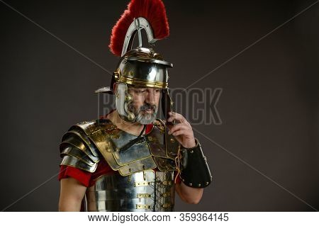 Roman soldier in actitude of reflection isolaed on a gray background