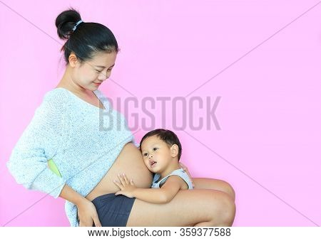 Asian Baby Boy Listening Baby In Tummy Of Pregnant Mother Isolated On Pink Background. Pregnancy And