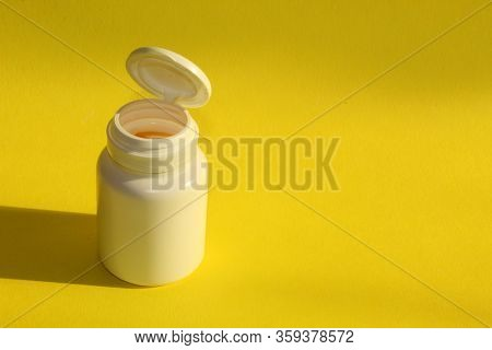 A Jar Of Medicine On A Yellow Background.