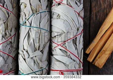 A Close Up Image Of Three White Sage Smudge Sticks And Palo Santo Sticks Used For Energy Clearing An