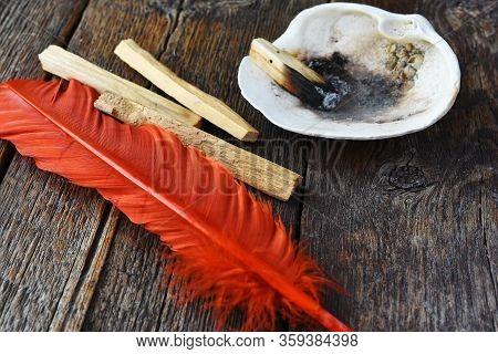 Palo Santo Smudge Sticks With A Bright Orange Sacred Feather.