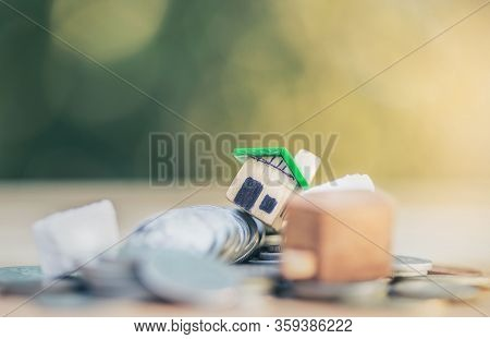 Mini House Model And Stack Of Coins. Business Risk Management. Property Investment And House Mortgag