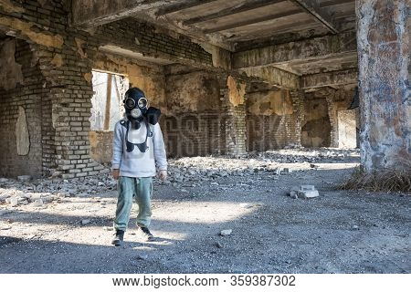 The Child In The Gas Mask On The Abandoned, Destroyed Brick Building.environment Pollution.apocalyps