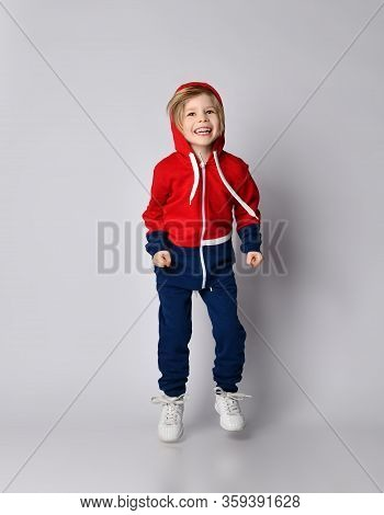 Full Growth Portrait Of Frolic Happy Laughing Blond Kid Boy In Red And Blue Hoodie And Pants Jumps,
