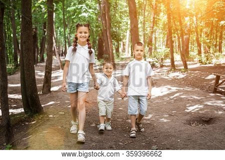 Happy Children Wearing White Shirts In Sunny Forest. Cute Girl Is Walking With Her Brothers. Concept