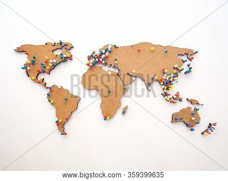 Colorful Pushpin For Marking Location At Wooden World Map On The White Concrete Wall.