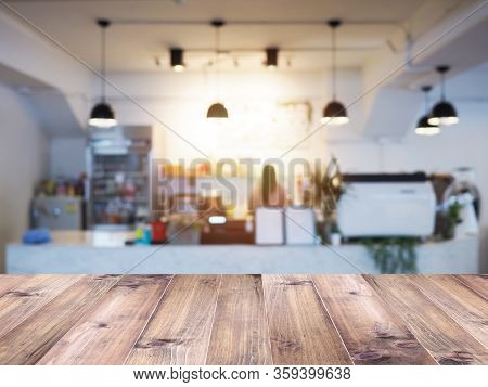 Wooden Table Top Over Abstract Blur Background Of Coffee Shop. Montage Picture Style To Display The