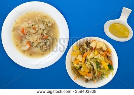 Cabbage Soup On A White Plate On A Blue Background. Soup With Vegetable Salad. Vegetarian Soup. Heal