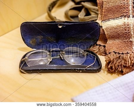 Vintage Eyeglasses In An Old Case On A Wooden Board Near Household Items Closeup