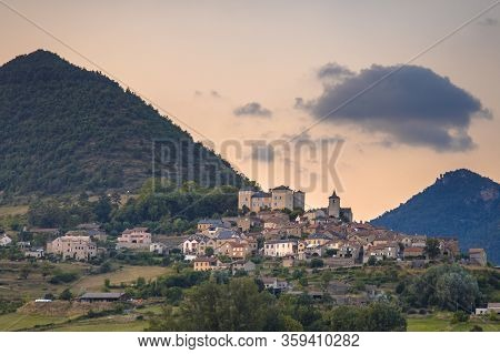 Hilltop Village In Cevennes Valley Landscape Near Le Rozier With Mountains And Hills Under Colorful