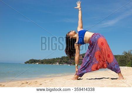 Asian Thai Woman Practicing Yoga In Haad Yao West Beach, Koh Phangan Island, Thailand