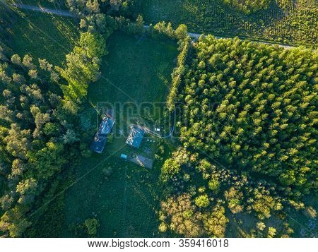 House In Forest Photographed From Above. Drone Landscape With Farm In Woods.