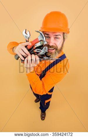 Repairment Tools. Smiling Worker Holds Repair Tools. Building. Industry. Technology. Spanner. Bearde