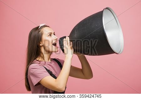 Young Activist Shouts Into A Megaphone, A Young Girl In A Jumpsuit On A Pink Background. Young Girl