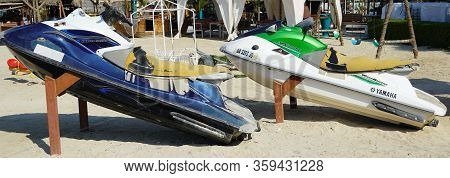 Two Colorful Jet Ski Parked On The Beach Of Holiday Season. Old Jet Skis On The Beach On Wooden Trai