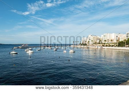 The Cityscape Of Bugibba City In Malta With A View At The Sea, Port, Palms, Apartments And The Dawre