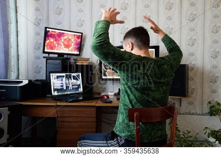 Krasnodar, Russia - April 02, 2020: A Man Sits At Computer Monitors And Is Horrified By The News Abo